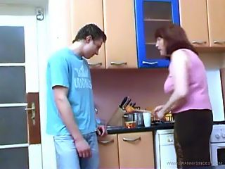 Horny guy pulls his grandma up onto the kitchen table and shags her wildly